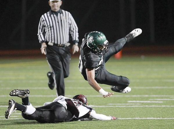 Costa Mesa's Oronde Crenshaw is tripped up by Katella's Ben Cobb during CIF Southern Section Southern Division first-round game Friday at Jim Scott Stadium.