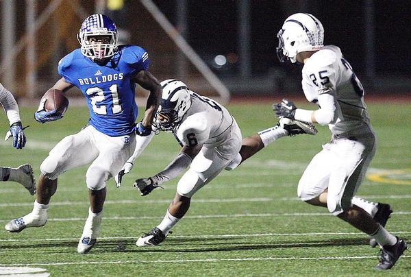 Burbank High's James Williams gets past Mayfair defenders Querale Hall and Derrick Reyes during a CIF-SS Southeast Division first round game at Memorial Field on Friday, November 15, 2013. Burbank blitzed Mayfair, 49-14. (Roger Wilson/Staff Photographer)