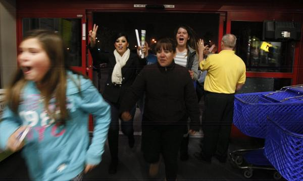 Shoppers run through the door at the stroke of midnight at Best Buy in Lakewood on Nov. 23, 2012.