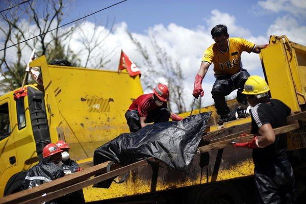 Workers load another body onto a truck for burial in a mass grave in Tacloban, Philippines, on Friday.