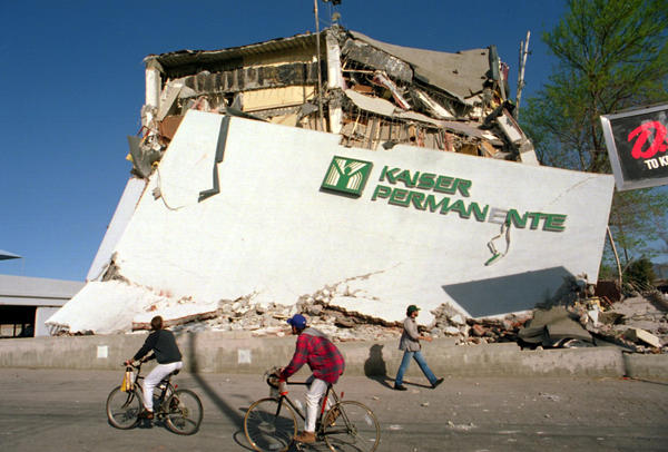 Cyclists roll past the remains of a collapsed Kaiser Permanente clinic and office building in Granada Hills.