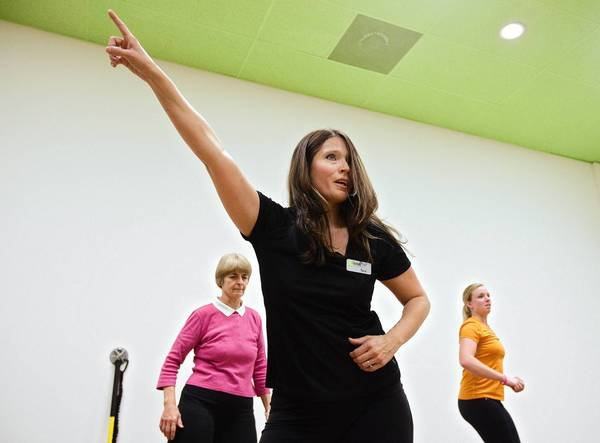 "Tara Briggs (center) leads a fitness dance class while Deb Grohs and Hanna Lyerly follow along at LWell, a new modern health club in Yorktown, on October 30. The club offers a variety of dance classes, including chair-oriented dance for participants with osteoarthritis of the knees. LWell co-founder Caroline Fornshell, a registered dietician and certified personal trainer, said these classes spice up an exercise routine. ""That makes fitness a little bit more relevant and funÑanybody can do it."""