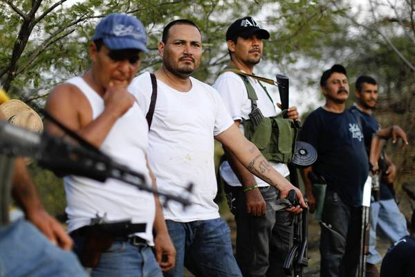 Vigilantes guard a checkpoint in the town of Las Colonias in Mexico's Michoacan state. Their enemy is the Knights Templar drug cartel.