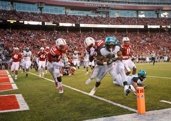Michigan State's Jeremy Langford scores after taking a hit from Nebraska's Corey Cooper.