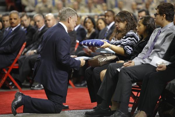 Ana Hernandez accepts the U.S. flag from acting Department of Homeland Security Secretary Rand Beers during the public memorial service for her husband, slain TSA officer Gerardo Hernandez.