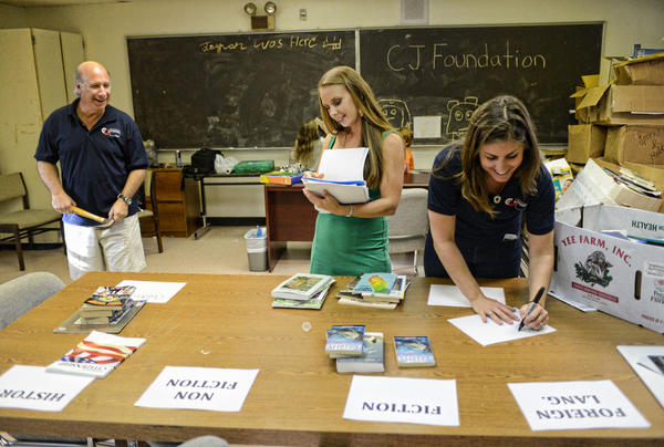 Volunteers Stephen Greene, from left, Sarah Staley and Stacey Staley help sort donated books for a new library that will open on the campus of Toussaint L'Ouverture High School in Delray Beach.