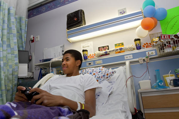 RaeKwon Harris, 13, plays XBox in his room at Children's Hospital of The King's Daughters in Norfolk on Nov. 12. After sustaining a spinal injury during a Peninsula Youth Football and Cheerleading Organization football game on Oct. 26, Harris has received an outpouring of support from other teams, parents and players. An announcer from the league brought Harris an XBox game station to use during his recovery in the hospital.