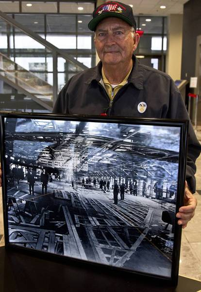 L.D. Joyner Sr. is holds a photo of the shipyard's old pattern shop. Joyner helped build the first USS John F. Kennedy.