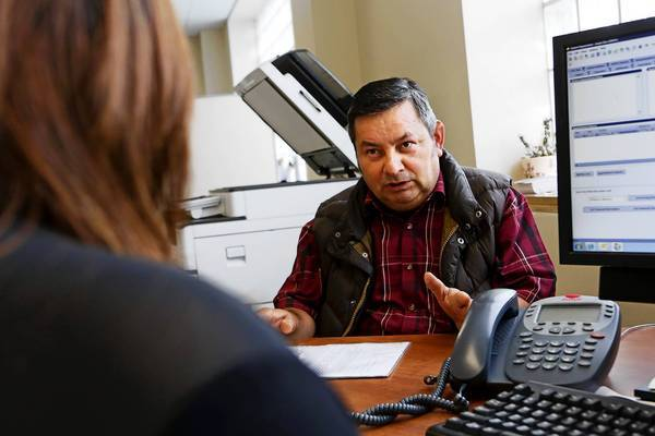 Angel Diaz, right, discusses which forms to fill out to enroll in healthcare coverage with Jessie Orozco at St. John's Well Child & Family Center in South L.A.