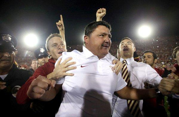USC interim Coach Ed Orgeron is mobbed by fans after the Trojans defeated the Stanford Cardinal, 20-17, on Saturday night at the Coliseum.