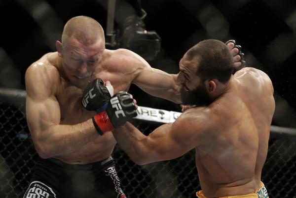 Georges St-Pierre, left, and Johny Hendricks land punches during their welterweight fight Saturday at UFC 167 in Las Vegas. St-Pierre won by split decision.