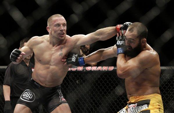 Georges St-Pierre, left, tags Johny Hendricks with a left hand during a welterweight bout Saturday at UFC 167 in Las Vegas.