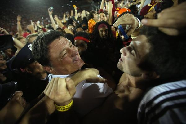 USC Trojans interim head coach Ed Orgeron celebrates the Trojans' 20-17 victory over the Stanford Cardinal as fans crowd onto the field at the Los Angeles Coliseum.