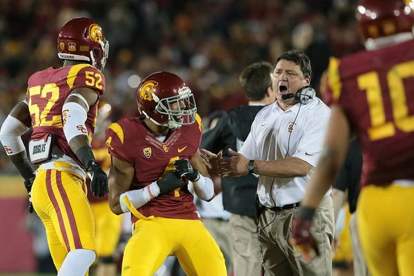 USC Interim Coach Ed Orgeron celebrates with cornerback Torin Harris, center, after the Trojans blocked a Stanford field-goal attempt in the second half of USC's 20-17 win Saturday.
