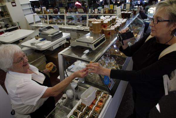 Doris Perez, left, 78, of Hollywood serves a sample of nut butter to Lea Budge, visiting from Australia, at Magee's Nut Shop at the Original Farmers Market in Los Angeles.