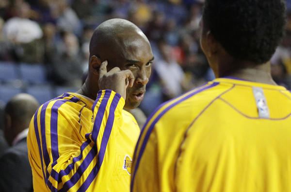 Lakers guard Kobe Bryant talks to teammate Nick Young before a preseason game.