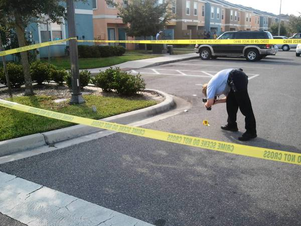 A crime scene investigator photographs shell casings Sunday afternoon in Orlando.