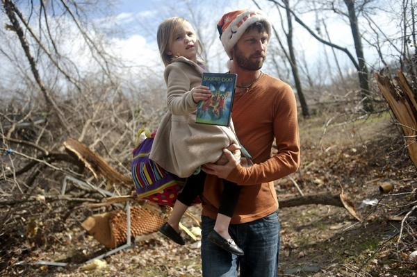 East Peoria resident Billy Vestal evacuates with his daughter, Lillian Vestal, 3, after a tornado damaged the area. Intense thunderstorms and tornadoes swept across the Midwest on Sunday, causing extensive damage in several central Illinois communities while sending people to their basements for shelter.