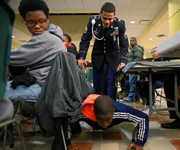 Staff Sgt. Jeremy Norris watches as Jaylen Anderson, 13, performs 20 push-ups during The Steve Harvey Mentoring Program for Young Men at Chicago State University Friday. A requirement for the weekend event is that participants come from homes without a positive male role model.