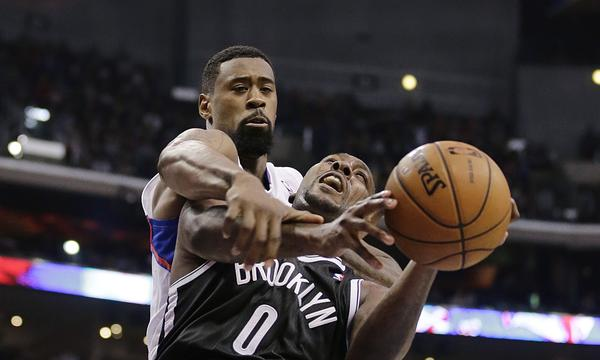 Clippers center DeAndre Jordan, left, fouls Brooklyn's Andray Blatche while trying to block a shot during Saturday's 110-103 win. Jordan's vocal demeanor plays a role in his effort to become the NBA's top defender.