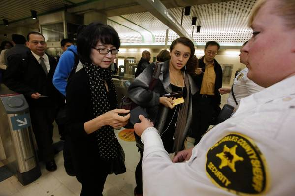 Los Angeles County Sheriff's Security Assistant April Ramirez checks commuters' TAP cards to ensure their subway fare was paid at the Civic Center/Grand Park station in downtown L.A.