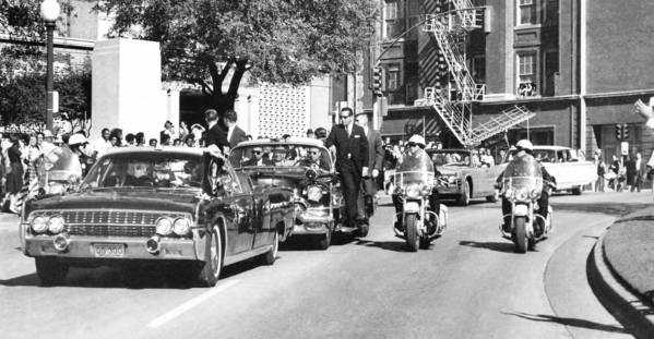 President Kennedy's limousine passes through Dealey Plaza on Nov. 22, 1963. News of the assassination was transmitted around the world by wire services.