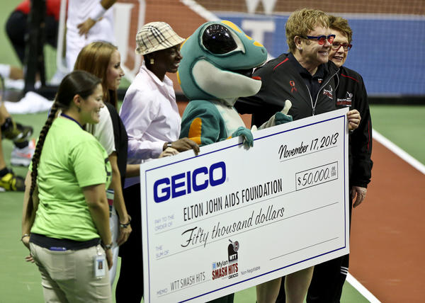 Sir Elton John and Billie Jean King stand with a check made out to the Elton John Aids Foundation during a break in actiom at The Mylan World Team Tennis Smash Hits celebrity tournament at the HP Field House at the ESPN WIde World of Sports Complex on Sunday, November 17, 2013.
