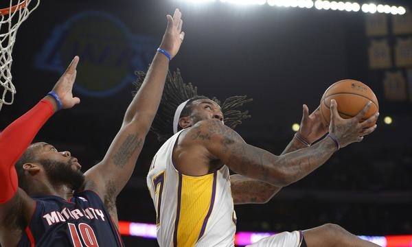 Lakers center Jordan Hill, right, puts up a shot over Detroit Pistons center Greg Monroe during the first half of Sunday's game at Staples Center.