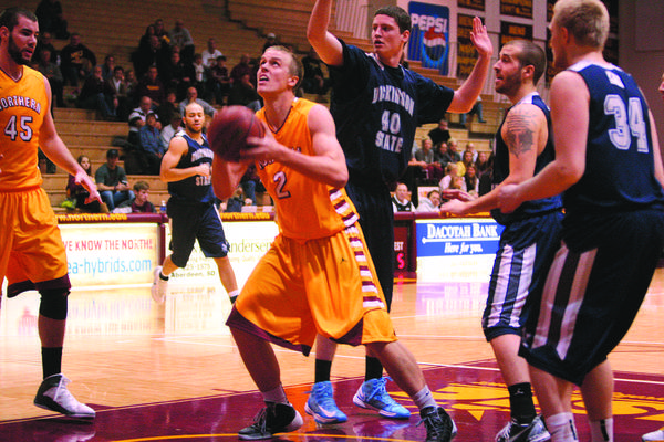 Northern State's Seth Bachand (2) puts up a shot against Dickinson State's Sean Kelly (40) on Sunday at Wachs Arena.