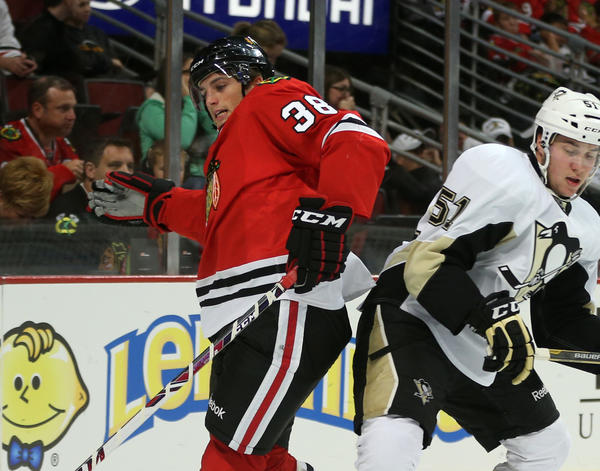 Blackhawks right wing Ryan Hartman (38) gets tangled up with Penguins defenseman Derrick Pouliot (51) in the first period of a preseason game at the United Center.