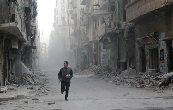 A rebel fighter from the Free Syrian Army runs in a street of Aleppo's Salah al-Din neighbourhood during fighting against Syrian government forces on Monday.