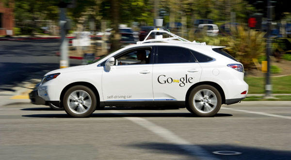 A man drives a Google Inc. self-driving car in front of the company's headquarters in Mountain View, Calif.