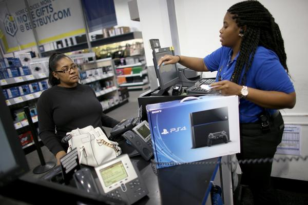Kimberly Lee, left, purchases a Sony Playstation 4 from Ashley Delva, a sales associate at Best Buy in in Pembroke Pines, Fla.