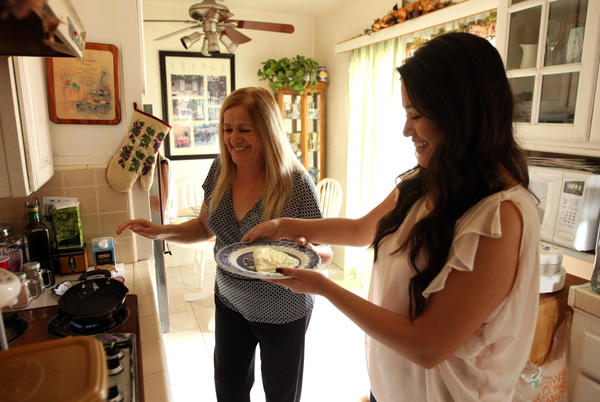 Genesis Tenorio, 22, right, receives a plate of food from her mother, Coco Tenorio, during breakfast at their El Monte home. Genesis Tenorio, a recent graduate of Loyola Marymount University, is living with her parents as she prepares to apply for law school.