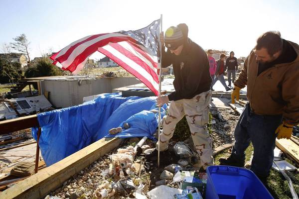 Jake Coyle of East Peoria, left, and John Mattern plant a flag as they dig out friends and relatives in the wake of a devastating tornado that struck Washington.