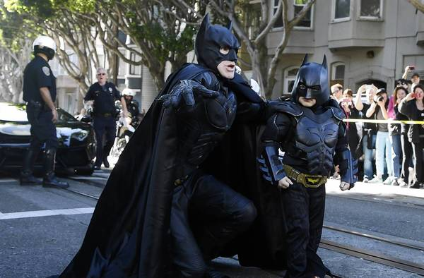 Five-year-old cancer survivor Miles Scott, dressed as Batkid, walks with Batman before saving a damsel in distress in San Francisco on Friday.