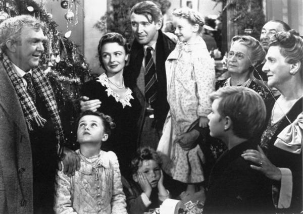 "James Stewart, center, as George Bailey is reunited with his wife, played by Donna Reed, left center, and their children during the final scene of Frank Capra's 1946 movie ""It's A Wonderful Life."" Stewart has his arm around child actress Karolyn Grimes, who played his daughter Zuzu. Actor Thomas Mitchell, as Uncle Billy, stands at left."