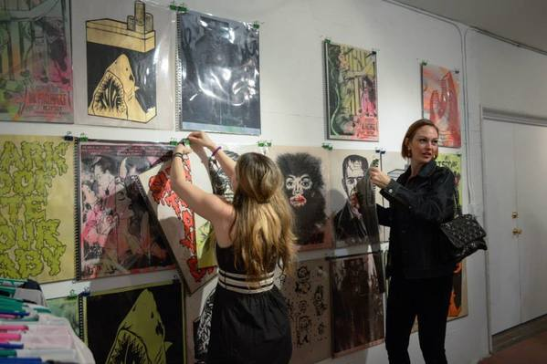 Gabba Gallery's Jamie Becker freshens up a wall of Shark Toof prints at Saturday's opening of Wish List.