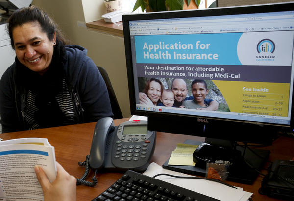 Marta Viera smiles as her application for Obamacare is completed by an enrollment counselor at St. John's Well Child and Family Center in Los Angeles.