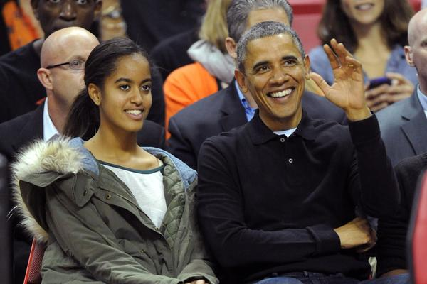 President Obama, with his daughter Malia, takes a break from the battle over his healthcare law by attending a basketball game Sunday between the Oregon State Beavers and the Maryland Terrapins in College Park, Md.