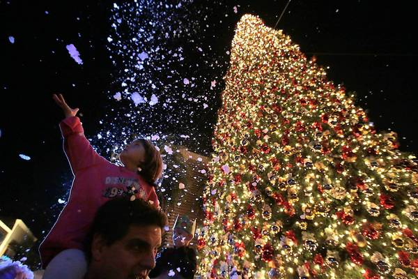 Lily Glasser, 4, reaches out for faux snow as she and her father Dan join thousands of others at the annual Christmas tree lighting at Fashion Island in Newport Beach. The 90-foot white fir, which cost roughly $1,000 per foot, came up 25 feet short of being the tallest in the region.