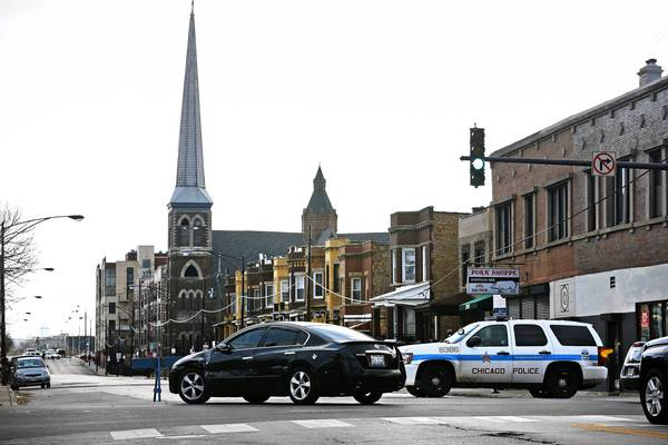 Chicago police at West Belmont and North California avenues keep traffic from heading east where Concordia Evangelical Lutheran Church's steeple was in danger of falling Monday after being damaged by heavy winds the day before.