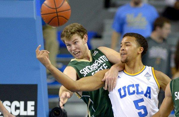 UCLA guard Kyle Anderson and Sacramento State forward Alex Tiffin battle for a loose ball in the first half Monday night at Pauley Pavilion.