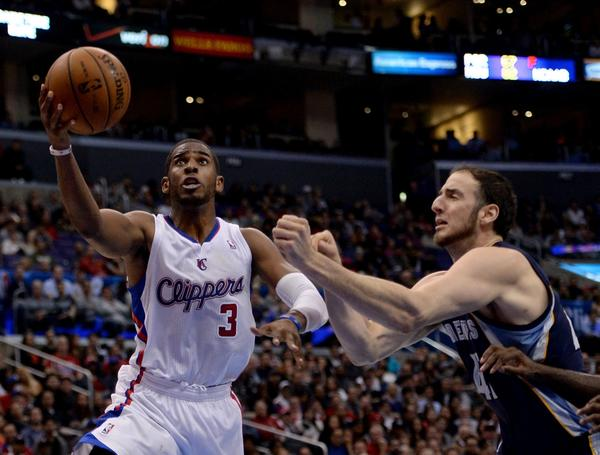 Clippers point guard Chris Paul gets to the basket for a layup and is fouled by Grizzlies center Kosta Koufos during their game Monday night.