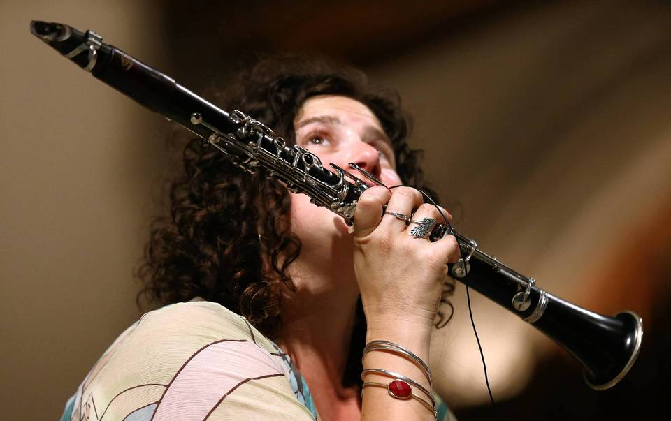 Clarinetist Anat Cohen speaks into a microphone attached to her clarinet during the 2013 Hyde Park Jazz Festival at the Rockefeller Chapel on the University of Chicago campus.