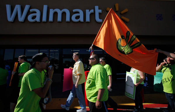 Anthony Goytia, a Wal-Mart employee, carries a flag as part of a protest in Paramount.