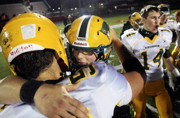 Stevenson's Willie Bourbon (right) hugs Stevenson's Jason Avvrick (55) after beating Barrington in their Class 8A IHSA playoff game at Barrington High School Saturday, Nov. 16 in Barrington.