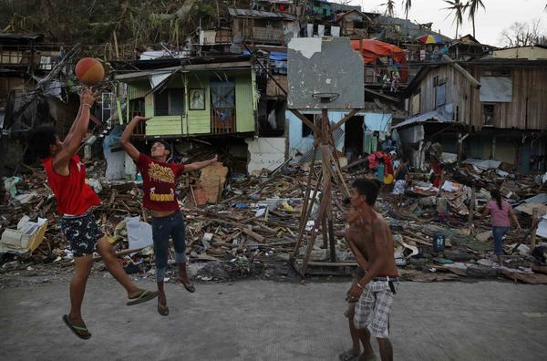 Residents play basketball with a makeshift net in an area destroyed in the aftermath of Typhoon Haiyan.