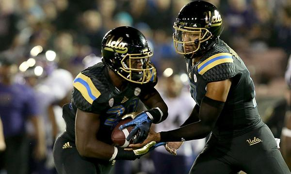 UCLA quarterback Brett Hundley hands off to Myles Jack during the Bruins' victory over Washington on Friday.