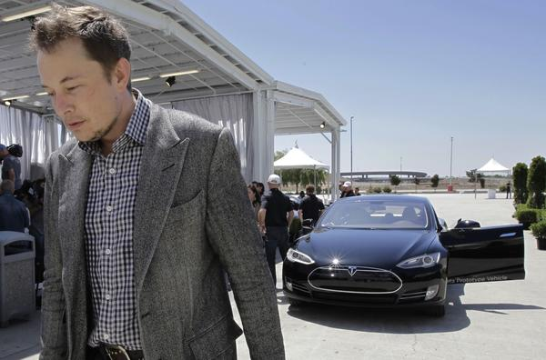 Tesla Chief Executive Elon Musk walks past a Tesla Model S after a 2012 news conference at the Tesla factory in Fremont, Calif. Three Model S hatchbacks have caught fire in recent months.
